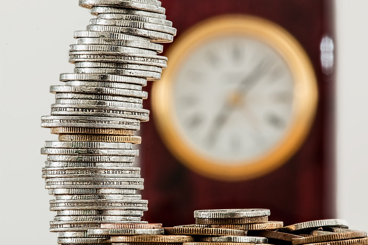 a stack of coins in focus in front of an out-of-focus analog wall clock